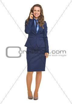 Full length portrait of smiling business woman talking cell phon