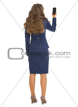 Full length portrait of business woman taking photo with cell ph