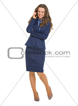 Full length portrait of smiling business woman talking mobile ph