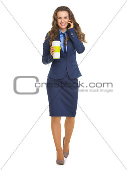 Full length portrait of happy business woman with cup of hot bev