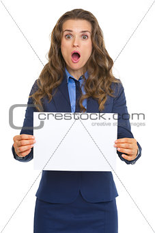 Surprised business woman showing blank paper sheet