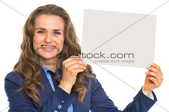 Smiling business woman showing blank paper sheet