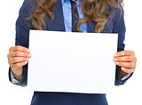 Closeup on business woman showing blank paper sheet