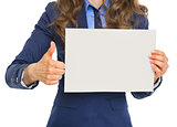 Closeup on business woman showing blank paper sheet and thumbs u