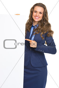 Smiling business woman pointing on blank billboard
