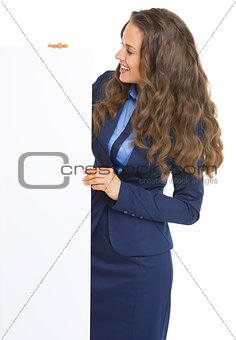 Smiling business woman looking on blank billboard