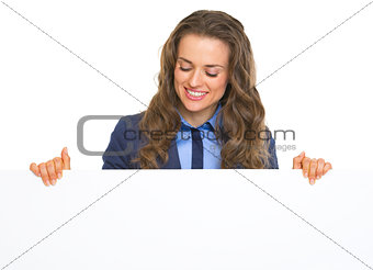 Happy business woman looking on blank billboard