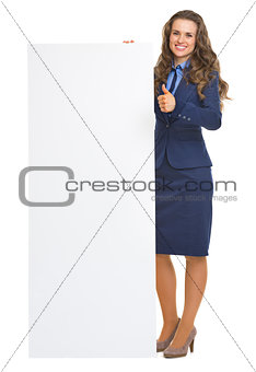 Full length portrait of smiling business woman showing blank bil