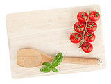 Cooking utensil and tomato with basil over cutting board
