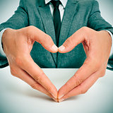 man in suit forming a heart with his hands
