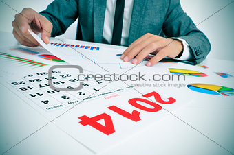 man in suit with charts and a 2014 calendar