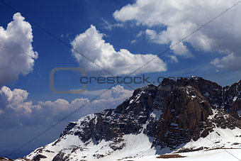 Blue sky with clouds and snow rocks