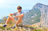 Young Man Traveler relaxing with Mountains on background Hiking and Healthy Lifestyle concept