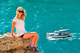 Young Woman relaxing on rocky cliff with blue Sea and Ship yacht on background Summer Traveling and Healthy Lifestyle concept