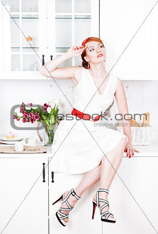 Beautiful woman sitting on the kitchen table