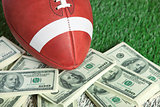 College style football on field with a pile of money