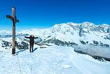 Tourist near the cross on winter mountain top