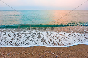 Splash of sea foam on a sandy beach