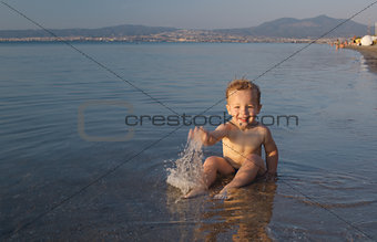 Cute little boy splashing in the sea