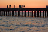 People on the old sea pier at sunset