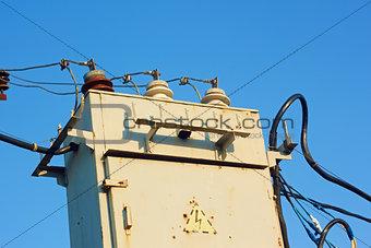 Old transformer against blue sky