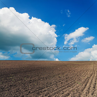 black ploughed field under blue sky with clouds