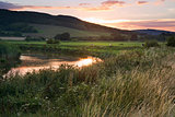 Summer sunset reflected in river in countryside landscape during