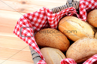 Fresh bread rolls in a rustic picnic basket