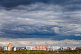 dark blue rainy clouds over city in autumn