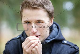 Young man warming hands with breathe