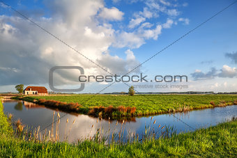 beautiful clouds over farmhouse and river