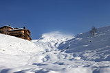Off-piste slope and hotel in winter mountains