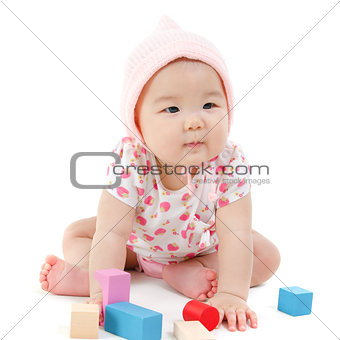 Asian baby girl playing wood blocks