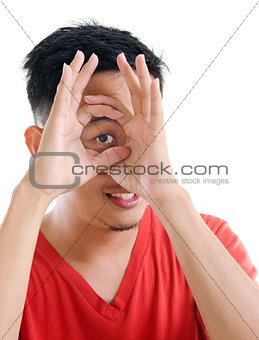 Asian man peeping through fingers hole