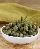 Pickled capers in white bowl on wooden table