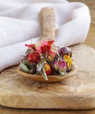 herbal tea from the dried flower buds of roses in a wooden spoon