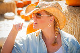 Beautiful Blond Female Rancher Wearing Cowboy Hat in Pumpkin Pat