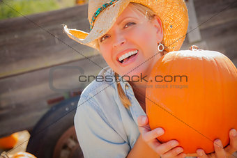 Beautiful Blond Female Rancher Wearing Cowboy Hat Holds a Pumpki