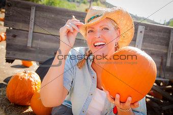 Beautiful Blond Female Rancher Wearing Cowboy Hat Holds a Pumpki