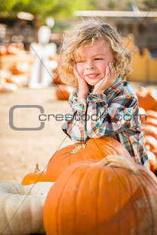 Little Boy Smiles While Leaning on Pumpkin at Pumpkin Patch