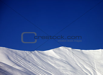 Off-piste slope and blue clear sky in nice winter day