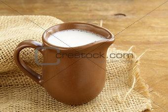 ceramic brown  jug full of milk