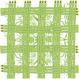 Grid of bamboo stalks on a background of green leaves