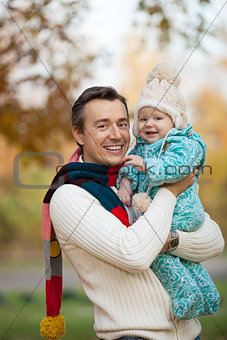 Portrait of young father and his little son in autumn park