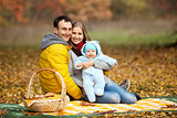 Young couple with baby boy on picnic in autumn park