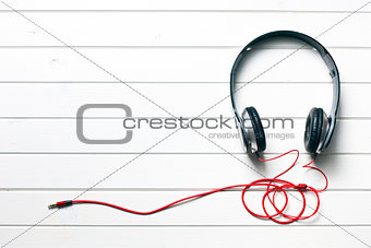 black headphones on white wooden table