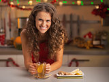 Smiling young woman drinking ginger tea in christmas decorated k