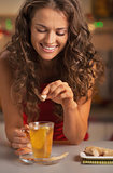 Smiling young woman adding cane sugar cube in ginger tea