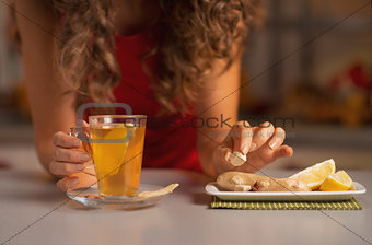 Closeup on young woman adding cane sugar cube in ginger tea