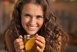 Smiling young woman drinking ginger tea with lemon